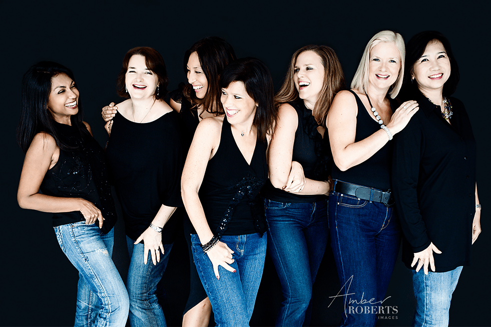 group of moms laughing together during photo shoot