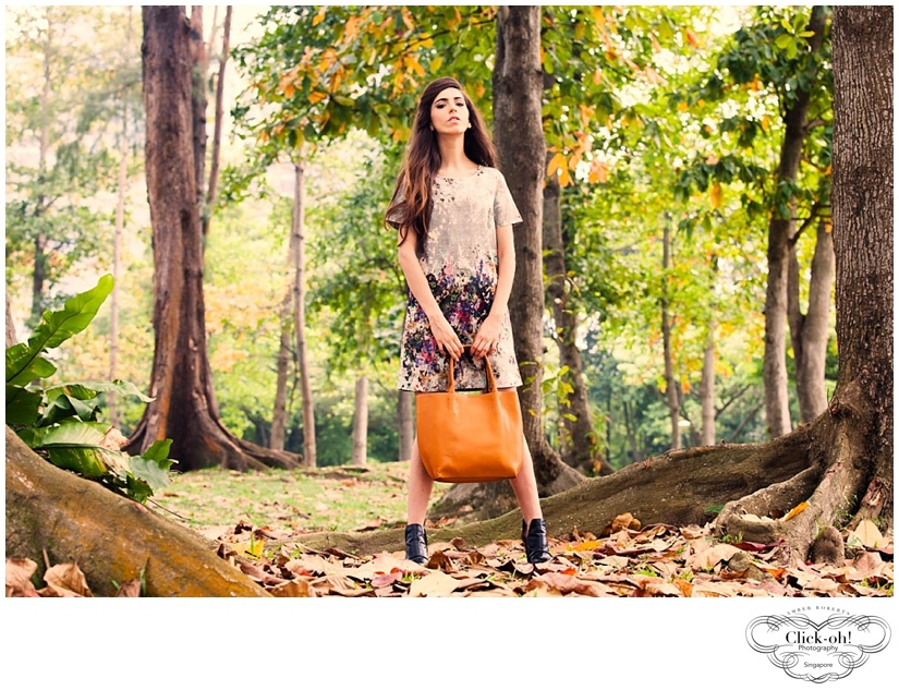 model with bag stands in singapore forest