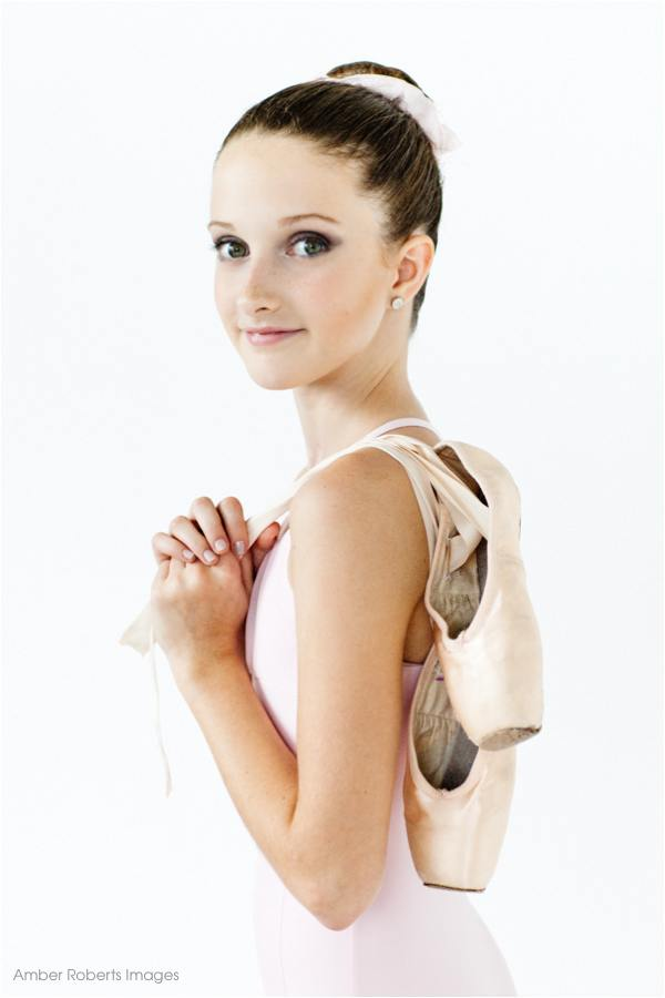 ballerina holds her pointe shoes in modern dance photo shoot minneapolis