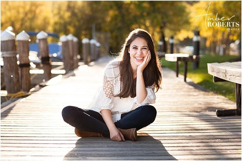 Laughing senior girl has pictures taken on boardwalk at Wayzata marina
