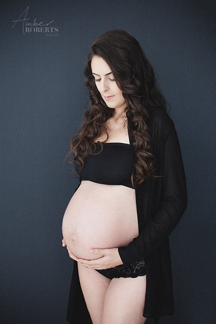 gorgeous lady wearing black embraces her belly in maternity photo session