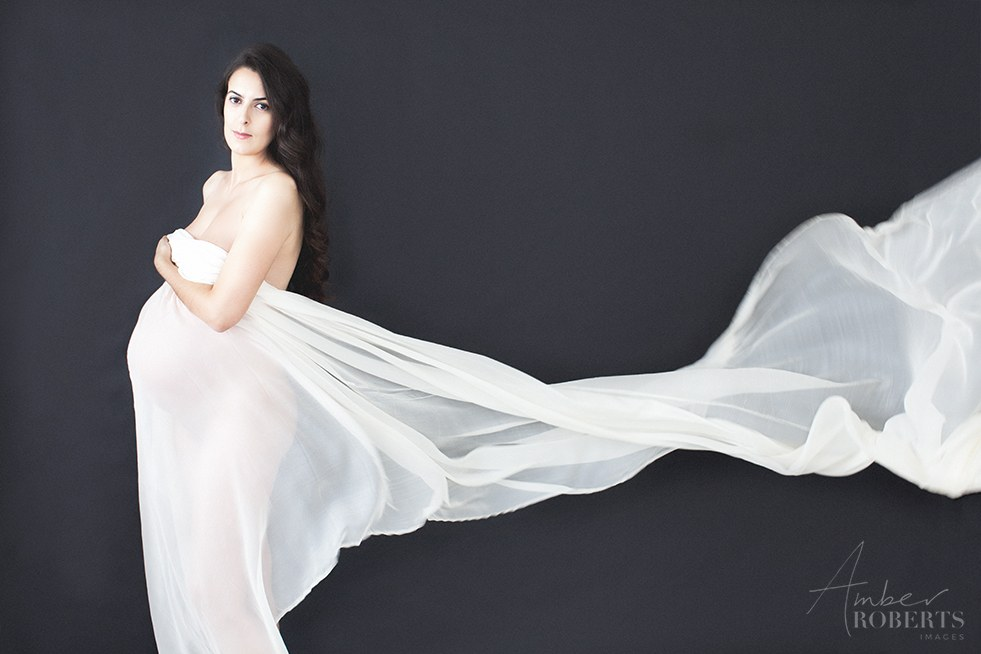 pregnant mama poses with billowing white silk in maternity photo session plymouth minneapolis minnesota